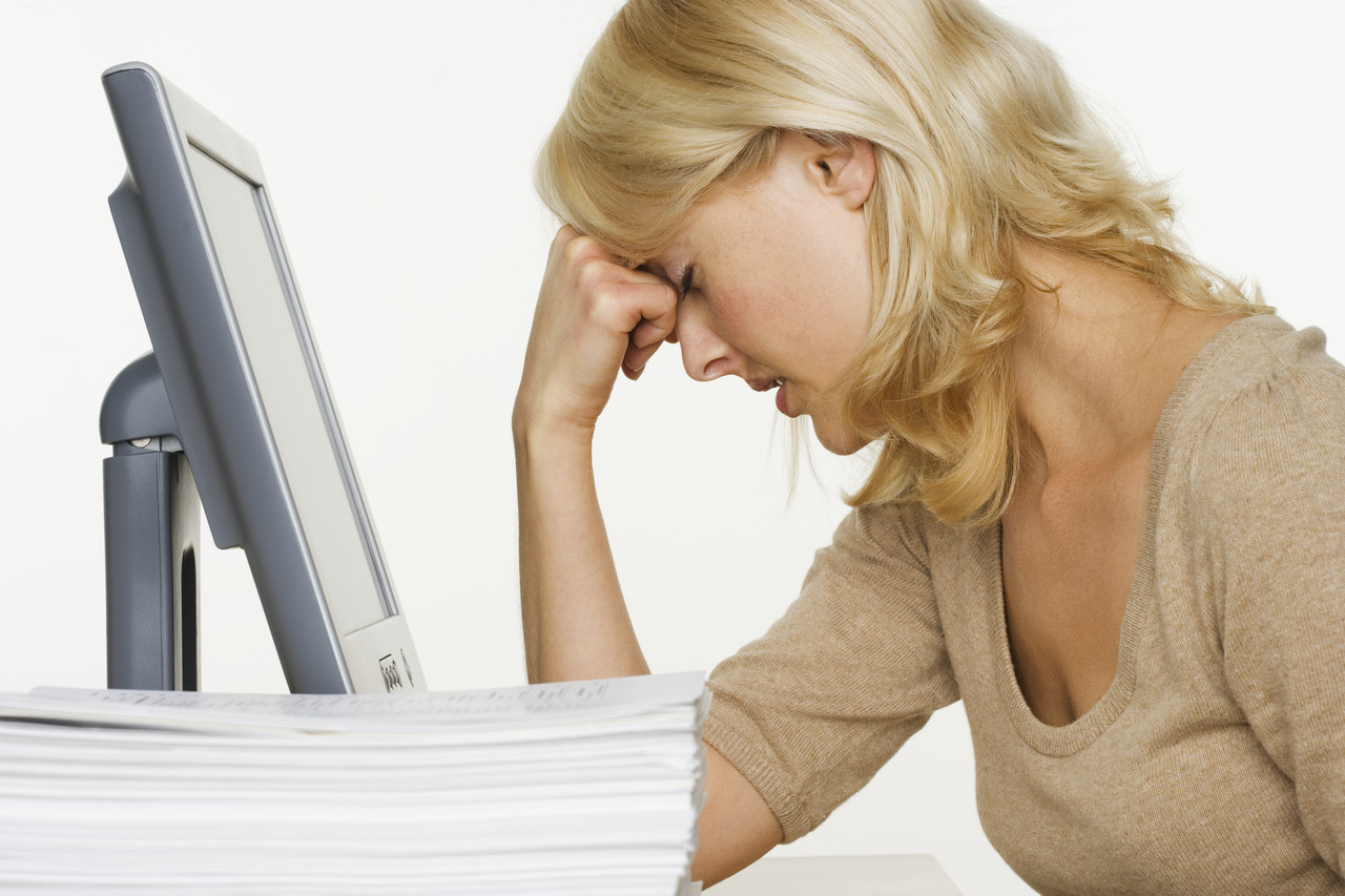 Woman at Computer With Stack of Paper
